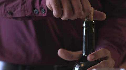 Man taking the cork out of a bottle of red wine Footage