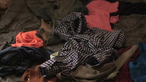 Clothes thrown on a pile of clothes in bed Live Action