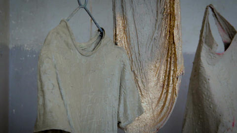 Clothes coated with concrete are hanging in the air Live Action