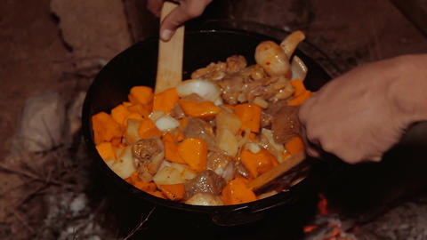 Cooking meal in cauldron on burning campfire at night Footage