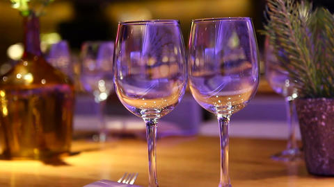 Empty wine glasses on a wooden table at a restaurant - Tilt up Footage