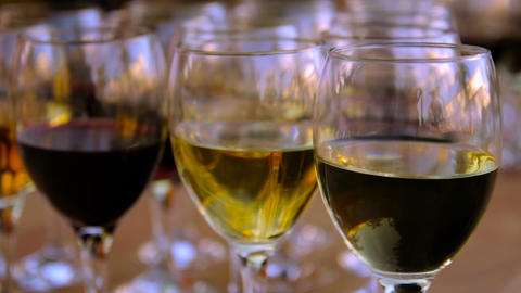 Glasses of red and white wine on a wooden table Footage