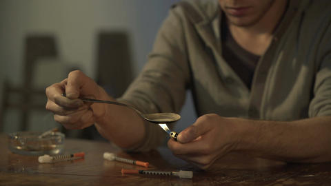 Male drug addict preparing heroin dose in spoon with lighter, syringes on table Live Action