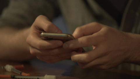 Young man lighting cigarette, drug and gaming addict playing on smartphone Live Action