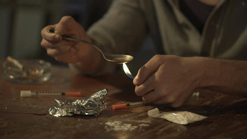 Young male withdrawing heroin dose with syringe from spoon, man abusing drugs Footage