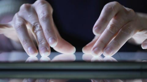 Woman shopping online on tablet pc, viewing goods, zooming images, hands closeup Footage