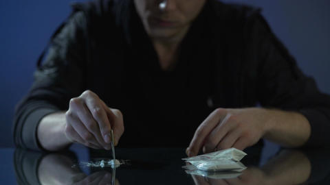 Drug addict forming cocaine lines on table, dangerous substance dependence Live Action