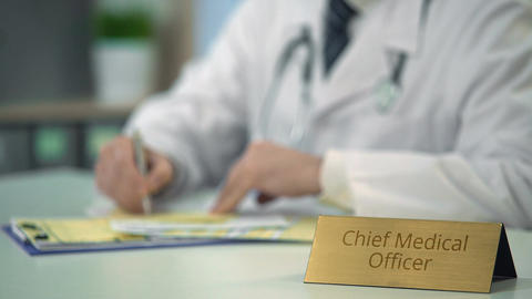 Chief medical officer completing report, prescribing medication in clinic Live Action
