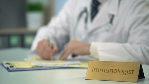 Immunologist writing down prescription, diagnosis, keeping medical records Footage