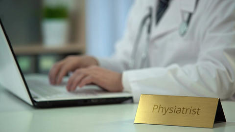 Physiatrist typing on laptop computer, completing monthly report in office Footage
