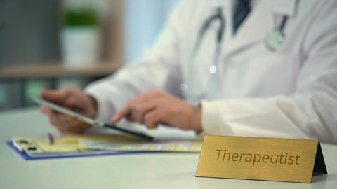 Therapeutist consulting patients online, scrolling medical news on tablet PC Footage