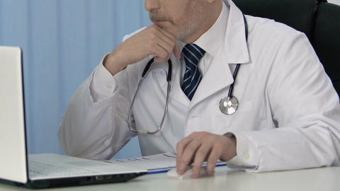 Male doctor working on laptop, inserting data in medical record for insurance Footage