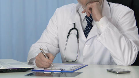 Professional physician writing treatment prescription in patient medical record Footage