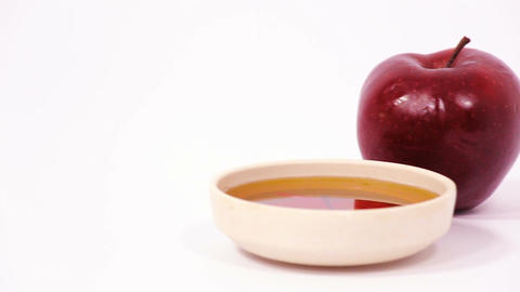 Red apple and bowl of honey isolated on a white background Filmmaterial