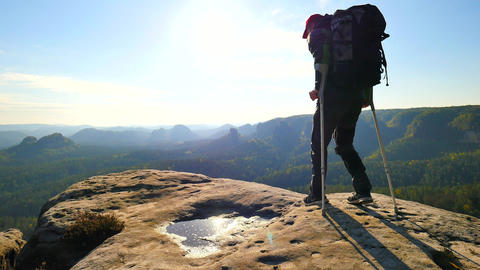 Tourist with medicine crutch above head achieved mountain peak. Hiker with broke Live Action