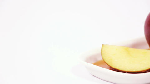 Red apple and red apple slice on white plate with honey isolated on a white back Footage