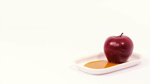 Red apple on white plate with honey isolated on a white background Live Action