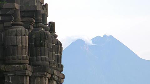 Prambanan Hindu temple complex against active volcano Mount Merapi. Indonesia Footage
