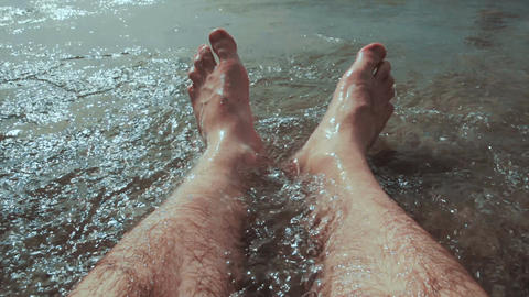 Caucasian man sitting in water and his legs are washed by the sea waves at the b Footage