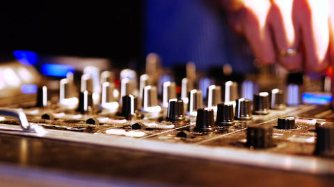Hands of DJ tweak various track controls on DJ mixer console at nightclub Live Action