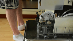 man gives dirty dishes in to the dishwasher Footage