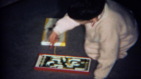 1969: Boy plays Tickle Bee board game on Christmas morning Footage
