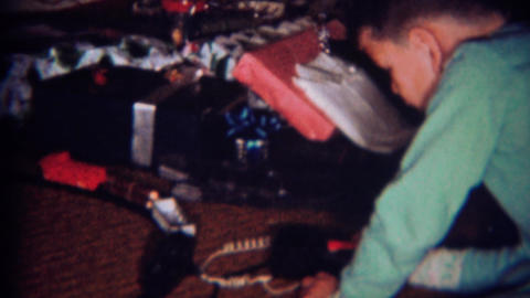 1961: Boy controls toy train set at Christmas time Footage
