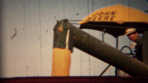 1951: John Deere harvester loading grain into transportation trucks Footage