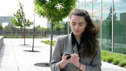 Business woman goes on the street, works on mobile and then phone Footage