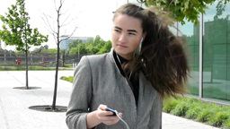 Bussines woman goes and listens to music on headphones before bussines building Footage