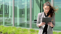 Business woman look to clipboard(paper) then smiles before business building Footage