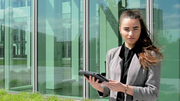 Business woman looks at tablet and then smiles before business building Footage