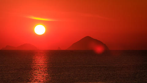 view of big sun disk sun-path across sea against blurry islands Footage