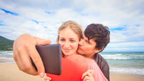 Guy Blond Girl Make Selfie Kiss Hide behind Red Heart on Beach Footage