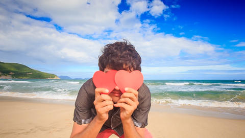 Guy Hides Face behind Red Hearts Smiles on Wave Surf Beach Footage