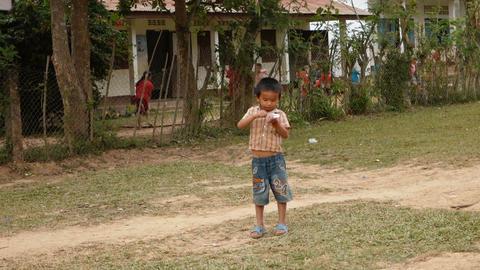 Street scene with little boy eating yogurt Acción en vivo