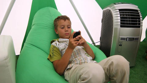 Motion along Boy Sitting in Chair and Playing Game on Smartphone Live Action