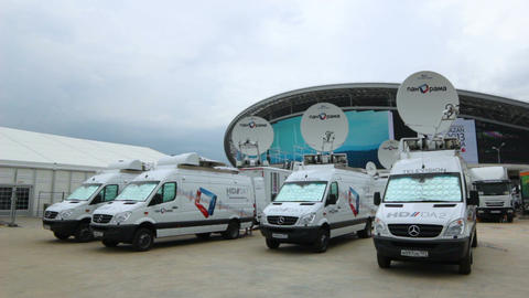 Mercedes Minibuses with Satellite Dishes near Modern Building Footage