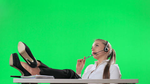 The secretary of the call center threw her legs on the table, green screen, alph Footage