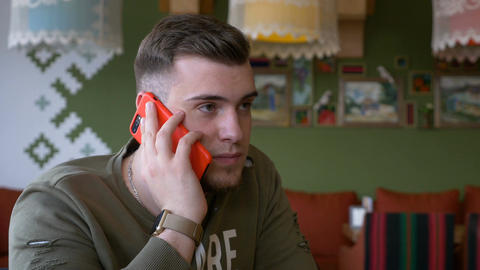 Young man having phone call conversation in the restaurant Footage