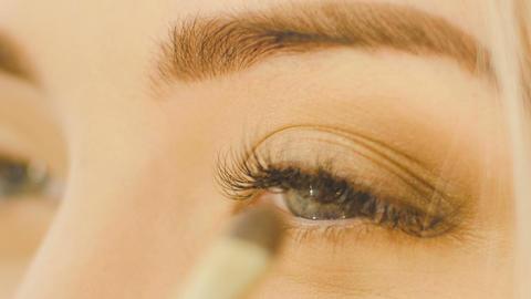 Professional Eye makeup artist applying eyeshadow powder. Beautiful woman face.  Footage
