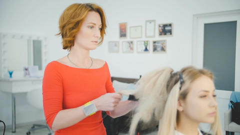 Female hairdresser of luxury beauty salon is standing and working with young blo Footage