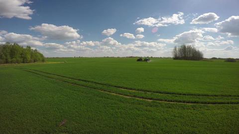 Tractor spraying green wheat field, 4K Footage