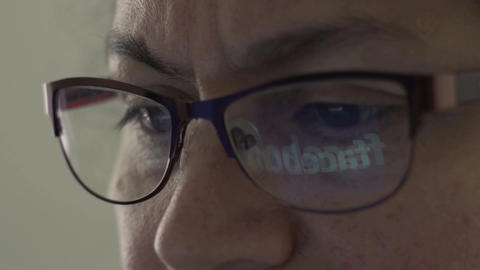 Facebook Logo Reflection in Glasses of Middle Aged Female Filmmaterial