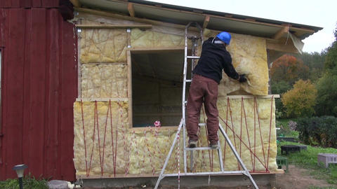 Worker insulating frame house wall with mineral wool Live Action