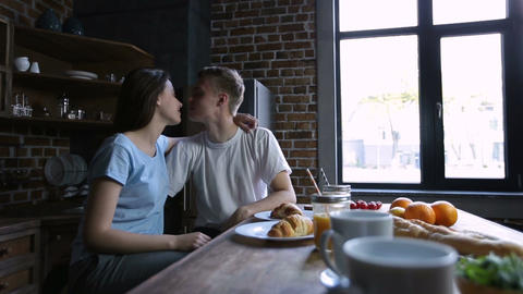 Happy young beautiful couple kissing in kitchen Footage