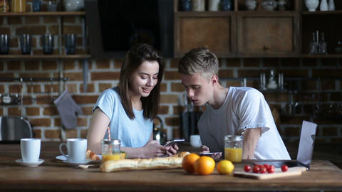 Couple eating breakfast whilst using mobile phones Footage