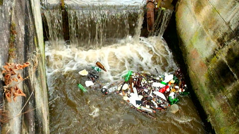 Slow motion. Plastic bottles and another mess turning on water level. Turning of Footage