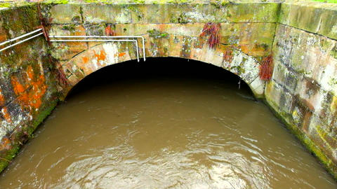Water of small river flow into small stony tunnel or bridge. Brown muddy water w Footage