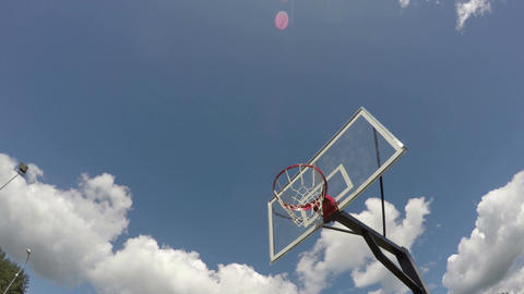 Basketball hoop against cloudy blue sky, time lapse 4k Footage
